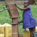 """Young African girl pumps water from a well in Uganda"""