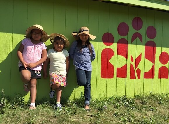 Jayla, Jaelie and Kaylie from Waywayseecappo First Nation learn against a green, wooden wall with the CFTC logo printed on it.