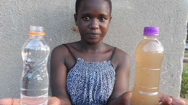 13-year-old Joan in Uganda shows a bottle with clean water and one with dirty water
