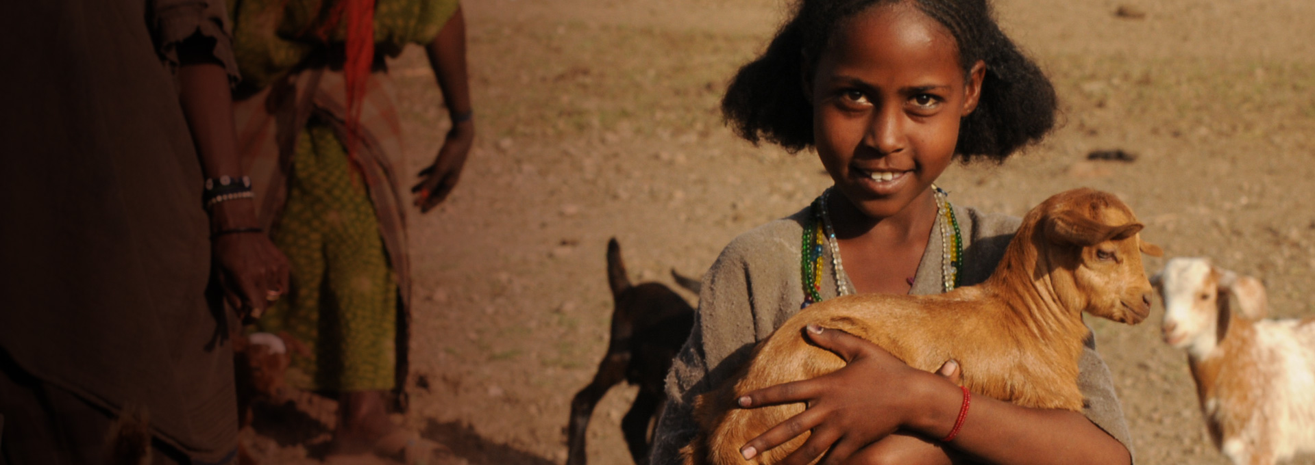 Girl in Africa holding a charity goat from Canadian Feed The Children